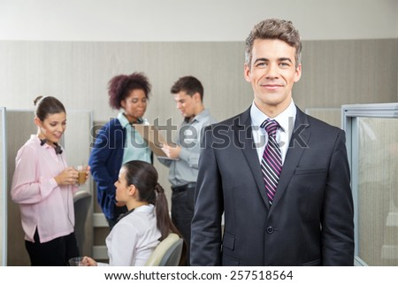 Portrait of confident manager with employees discussing in background at call center - stock photo