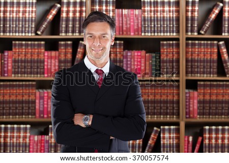 Portrait of confident mature attorney standing arms crossed against bookshelf in office - stock photo