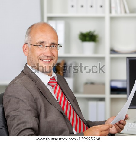 Portrait of confident mature businessman holding document in office - stock photo