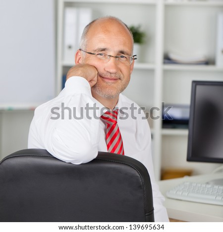 Portrait of confident mature businessman sitting on chair at desk in office - stock photo