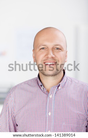 Portrait of confident mature businessman smiling in office - stock photo