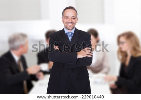 Portrait of confident mature businessman standing arms crossed against colleagues in boardroom - stock photo