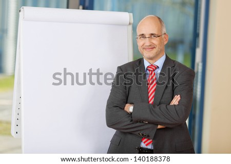Portrait of confident mature businessman with arms crossed standing by flipchart in office - stock photo
