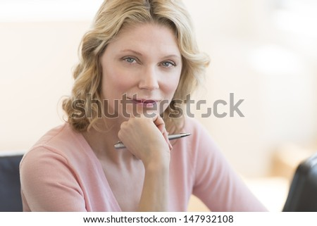 Portrait of confident mature businesswoman with hand on chin in office - stock photo