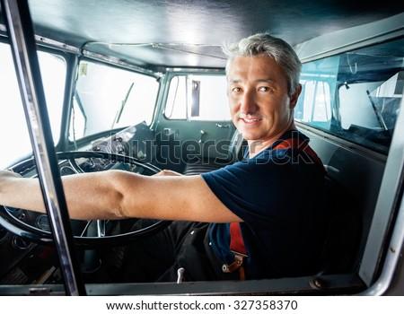 Portrait of confident mature fireman driving firetruck at station - stock photo