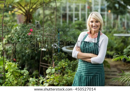 Portrait of confident mature gardener standing by plants