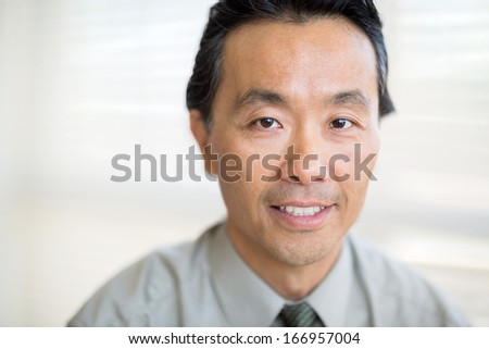 Portrait of confident mature male cancer specialist smiling in hospital - stock photo