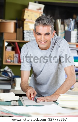 Portrait of confident mature male worker cutting paper at table in factory