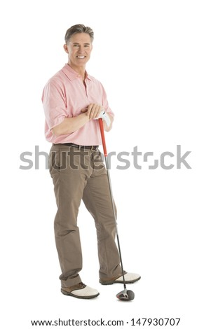 Portrait of confident mature man standing with golf club against white background