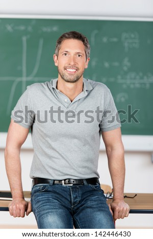 Portrait of confident mature teacher leaning on bench in classroom - stock photo
