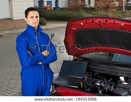 Portrait of confident mechanic with arms crossed holding wrench by car on street - stock photo