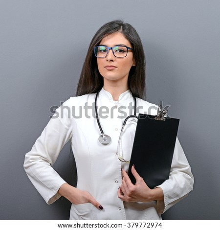 Portrait of confident medical doctor woman holding clipboard against gray background - stock photo