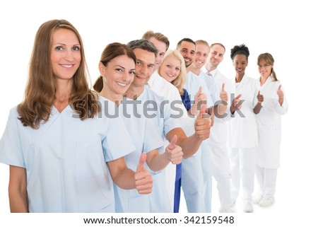 Portrait of confident medical team showing thumbs up while standing in line against white background - stock photo