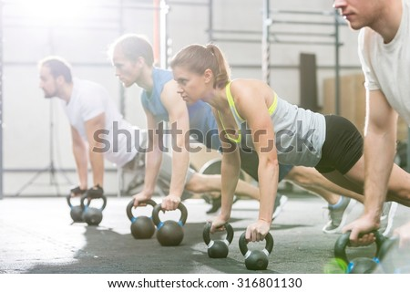 Portrait of confident men and women standing at gym - stock photo