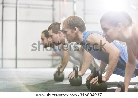 Portrait of confident men and women standing at gym