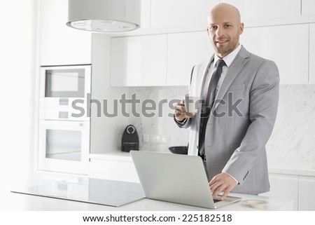 Portrait of confident mid adult businessman having coffee while using laptop in kitchen - stock photo