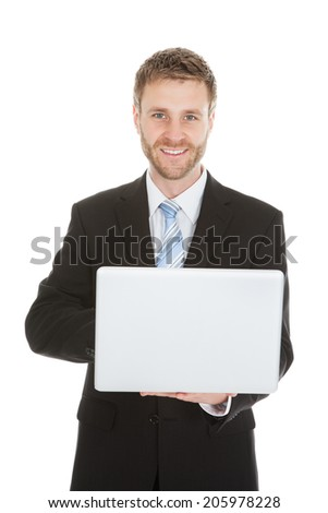 Portrait of confident mid adult businessman holding laptop over white background - stock photo