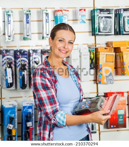 Portrait of confident mid adult female customer holding packed product in hardware store - stock photo