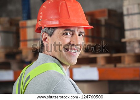Portrait of confident mid adult foreman at warehouse - stock photo