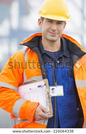 Portrait of confident mid adult man with clipboard in shipping yard - stock photo