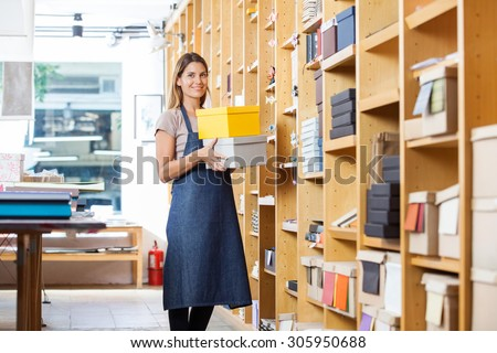 Portrait of confident mid adult woman carrying boxes in store - stock photo