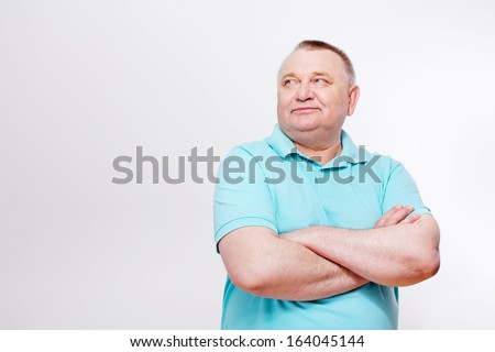 Portrait of confident middle aged man with crossed hands looking aside over white background