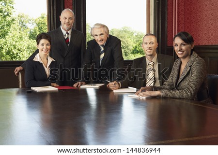 Portrait of confident multiethnic business team at conference table - stock photo