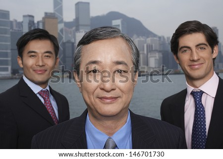 Portrait of confident multiethnic businessmen with cityscape in background - stock photo