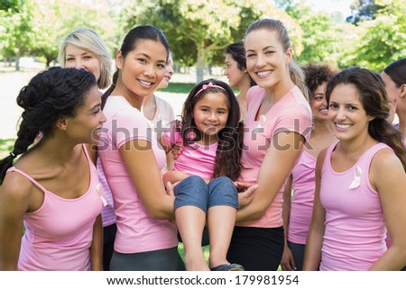 Portrait of confident multiethnic women carrying girl during breast cancer awareness at park - stock photo