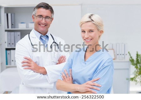 Portrait of confident nurse and doctor standing arms crossed at clinic - stock photo
