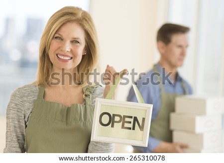 Portrait of confident owner wearing apron while holding open sign in coffeeshop - stock photo