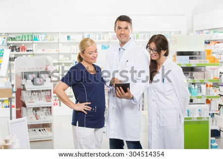 Portrait of confident pharmacist using digital tablet with coworkers in pharmacy - stock photo