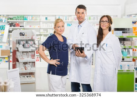 Portrait of confident pharmacists with digital tablet standing in pharmacy - stock photo