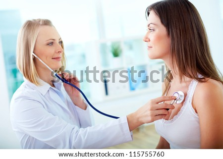 Portrait of confident practitioner checking heart beat of patient - stock photo
