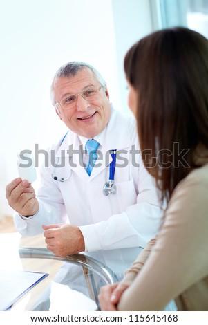 Portrait of confident practitioner prescribing vitamins to patient in hospital - stock photo