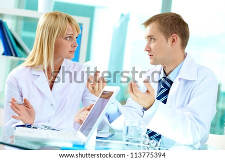 Portrait of confident practitioner showing different vitamins to his colleague