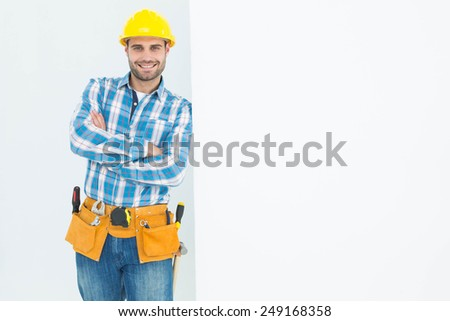 Portrait of confident repairman leaning on blank billboard on white background - stock photo