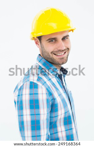 Portrait of confident repairman wearing hard hat on white background - stock photo