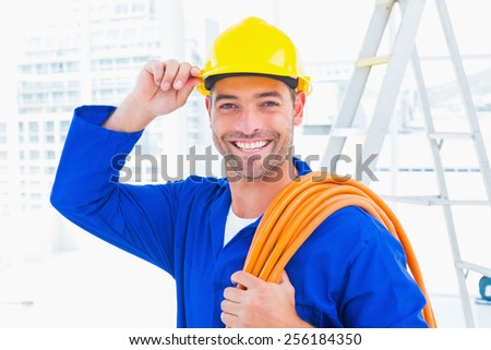 Portrait of confident repairman wearing hard hat while holding wire roll in bright office - stock photo