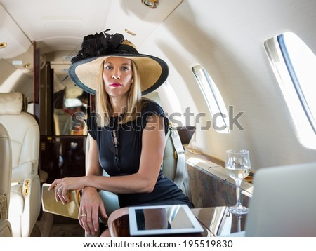 Portrait of confident rich woman sitting in private jet - stock photo