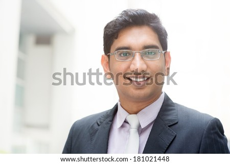 Portrait of confident 30s Asian Indian businessman smiling. India male business man, real modern office building as background. - stock photo