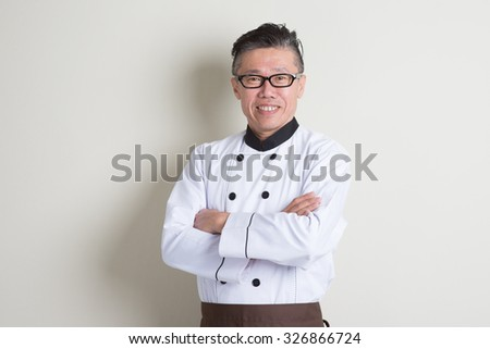 Portrait of confident 50s mature Asian male chef in uniform arms crossed, standing on plain background with shadow, copy space. - stock photo