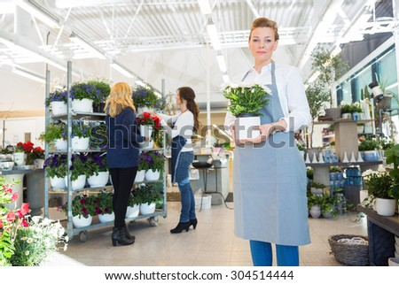 Portrait of confident salesgirl holding flower pot with customer and colleague in background at shop - stock photo