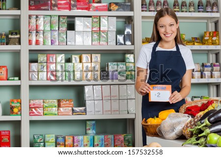 Portrait of confident saleswoman displaying pricetag in grocery store - stock photo