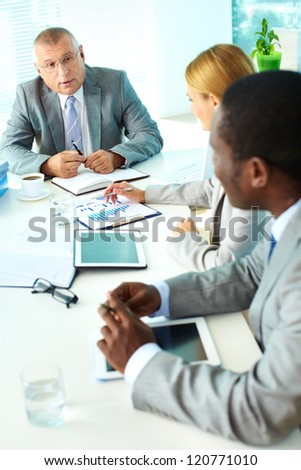 Portrait of confident senior boss looking at his employees at meeting - stock photo