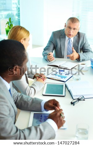 Portrait of confident senior boss looking at his employees at meeting