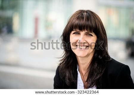 Portrait of confident senior business woman with office building in background - stock photo