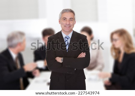 Portrait of confident senior businessman standing arms crossed against colleagues in meeting room - stock photo