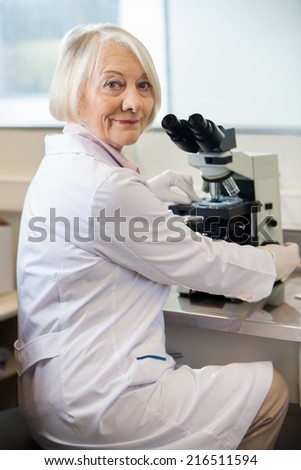 Portrait of confident senior female scientist using microscope in lab - stock photo