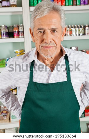 Portrait of confident senior male owner standing in grocery store - stock photo